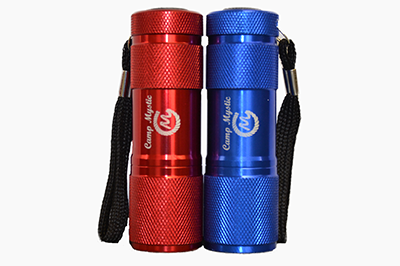 "NEW! Metal Flashlight - $6.00  Red or blue flashlight with ""Camp Mystic"" rope logo. AAA batteries included."